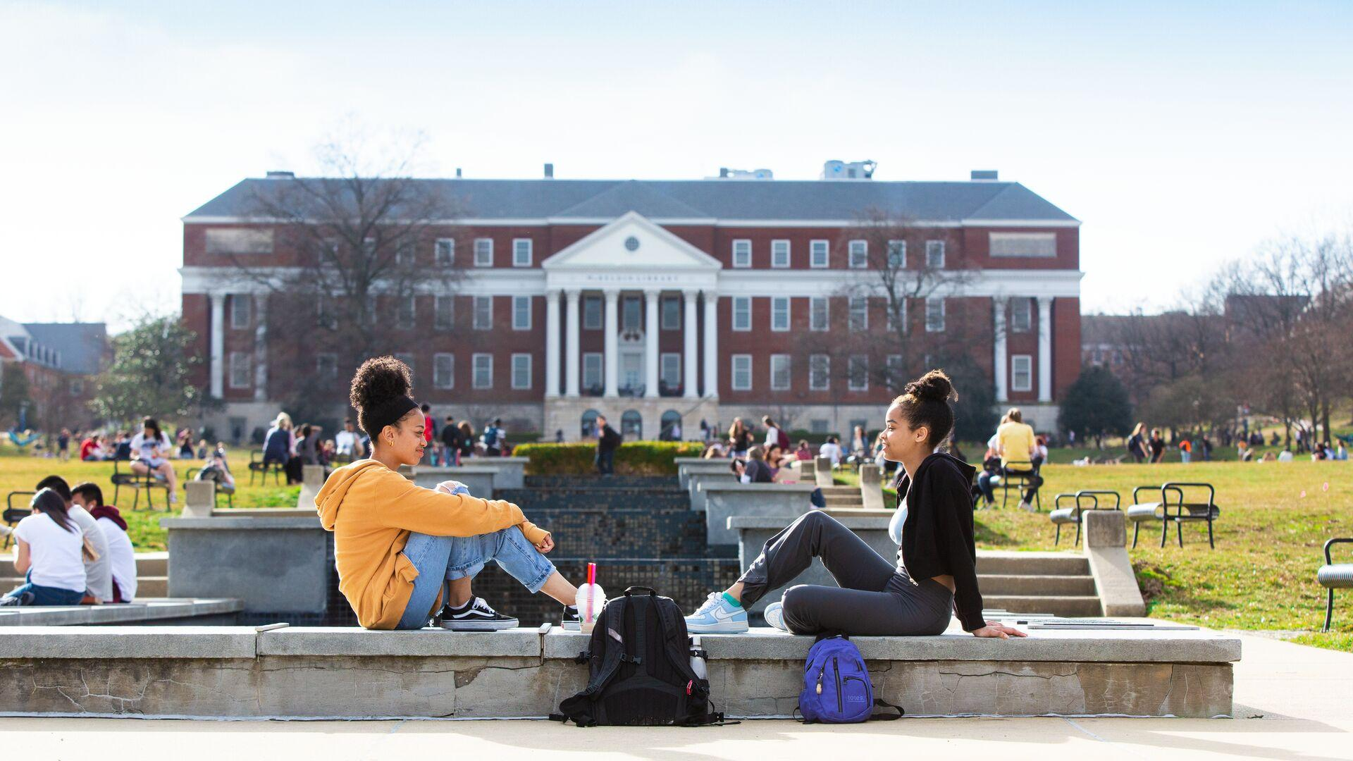 Two female students sitting along ODK Fountain with McKeldin Library in the background.